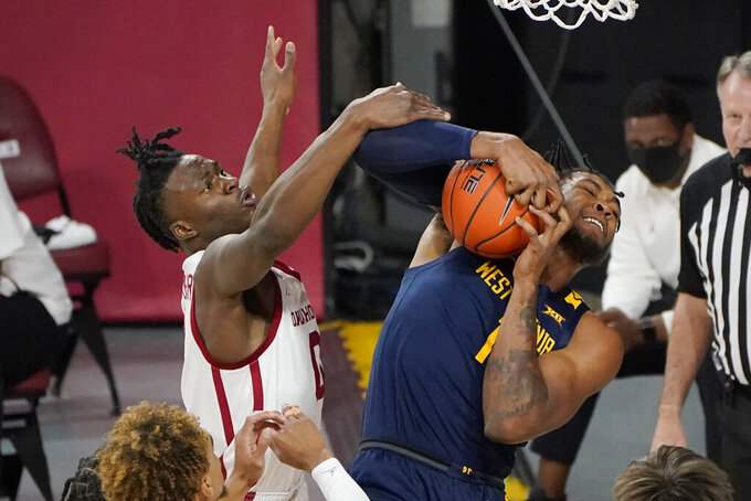 West Virginia forward Derek Culver (1) grabs a rebound in front of Oklahoma forward Victor Iwuakor (0) in the first half of an NCAA college basketball game Saturday, Jan. 2, 2021, in Norman, Okla. (AP Photo/Sue Ogrocki)