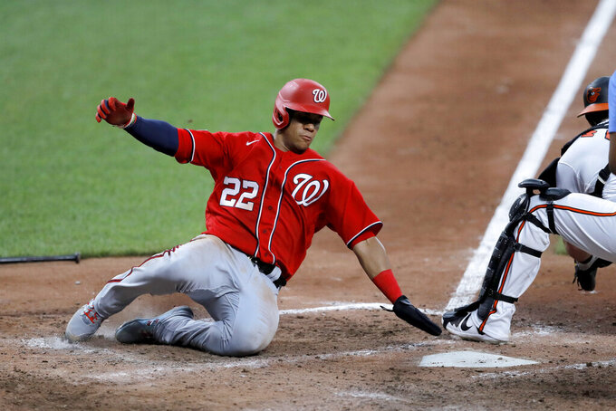 Washington Nationals' Juan Soto, left, slides in ahead of a tag by Baltimore Orioles catcher Austin Wynns while scoring on a double by Howie Kendrick during an exhibition baseball game Monday, July 20, 2020, in Baltimore. (AP Photo/Julio Cortez)