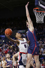Gonzaga guard Geno Crandall (0) shoots while defended by Saint Mary's center Jordan Hunter during the first half of an NCAA college basketball game in Spokane, Wash., Saturday, Feb. 9, 2019. (AP Photo/Young Kwak)