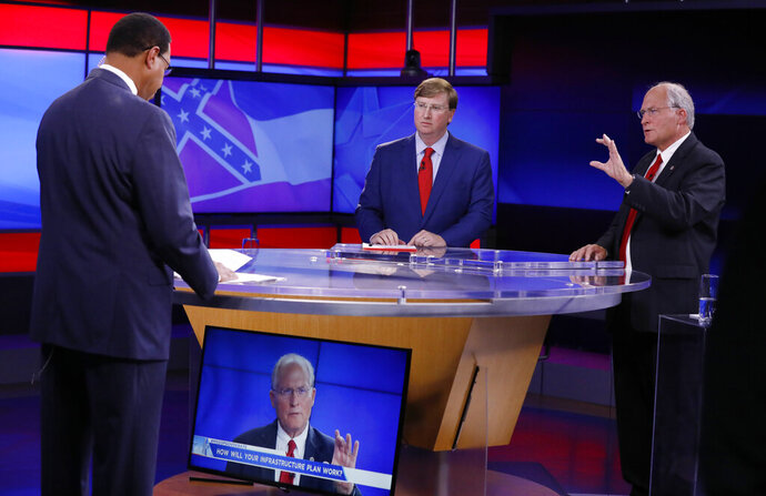 Former Mississippi Supreme Court Chief Justice and Republican gubernatorial candidate Bill Waller Jr., right, answer a question from WJTV co-anchor Byron Brown, left, during a GOP gubernatorial runoff debate against Lt. Gov. Tate Reeves, center, in Jackson, Miss., Wednesday, Aug. 21, 2019. (AP Photo/Rogelio V. Solis)