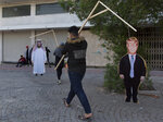 Activists carry cardboard cutouts that depicts US President Donald Trump that is hung to a gallows, during a rally for the Shiite group Asaib Ahl al-Haq, in Baghdad, Iraq, Saturday, Dec. 14, 2019.   (AP Photo/Nasser Nasser)