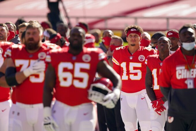 The Kansas City Chiefs and quarterback Patrick Mahomes (15) stand during the playing of the national anthem before the first half of an NFL football game against the New York Jets on Sunday, Nov. 1, 2020, in Kansas City, Mo. (AP Photo/Charlie Riedel)