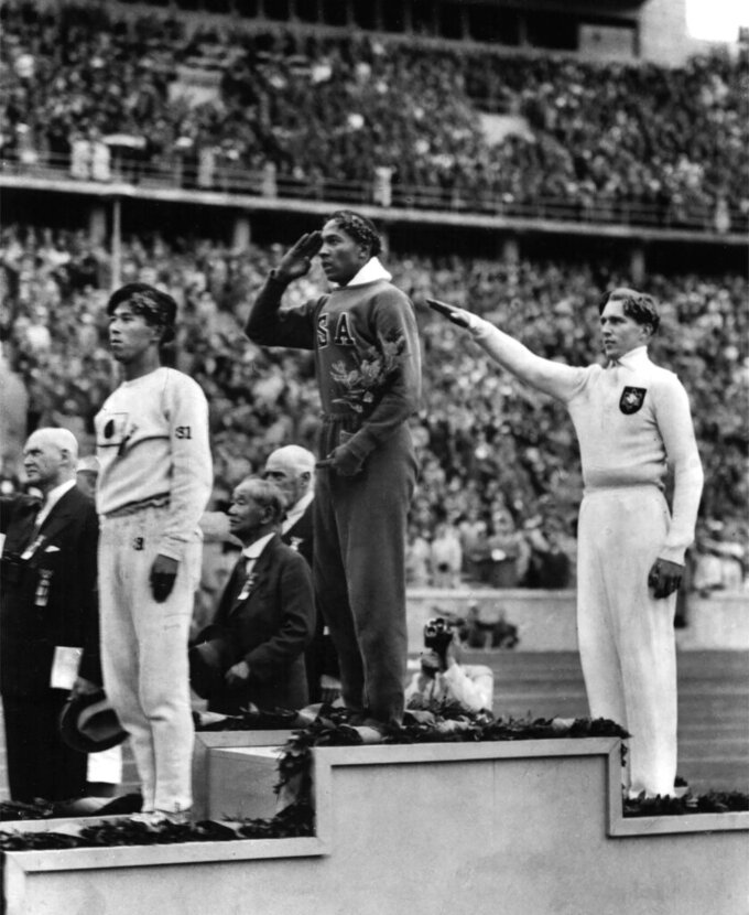 FILE - In this Aug. 11, 1936, file photo, America's Jesse Owens, center, salutes during the presentation of his gold medal for the long jump, after defeating Nazi Germany's Lutz Long, right, during the 1936 Summer Olympics in Berlin. Naoto Tajima of Japan, left, placed third. The performance of Jesse Owens will be honored in the stadium where he won four gold medals at the 1936 Olympic Games when the world championships are held in Berlin this month. (AP Photo/File)