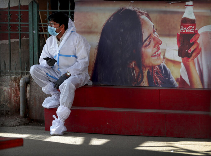 A health worker wearing personal protective equipment takes a break as he awaits travelers to arrive outside a a train station in Bengaluru, India, Monday, Feb. 22, 2021. Cases of COVID-19 are increasing in some parts of India after months of a steady nationwide decline, prompting authorities to impose lockdowns and other virus restrictions. (AP Photo/Aijaz Rahi)