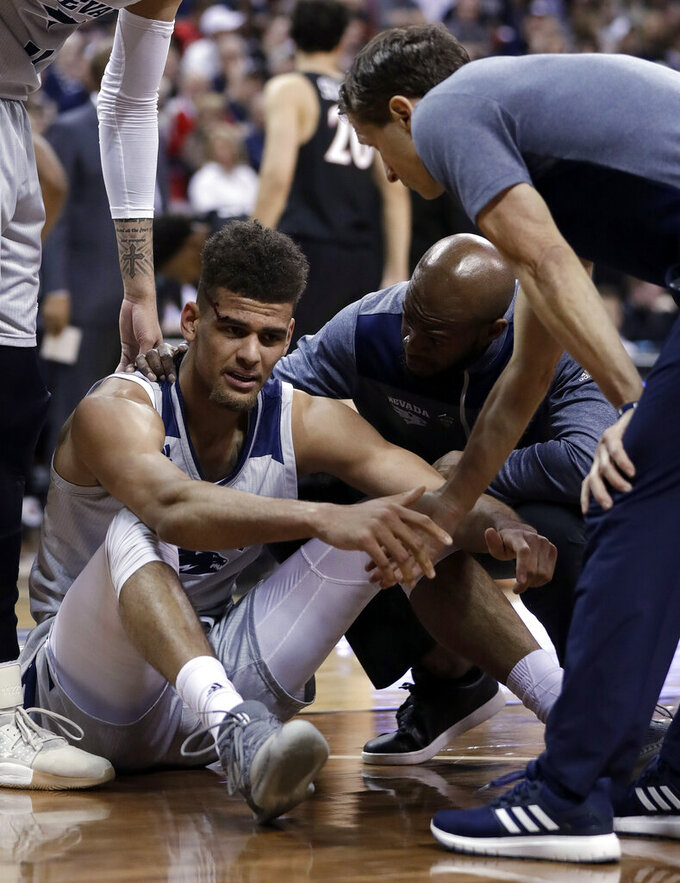 Nevada coach Eric Musselman, right, helps Trey Porter up from the court after a fall during the first half of the team's NCAA college basketball game against San Diego State in the Mountain West Conference men's tournament Friday, March 15, 2019, in Las Vegas. (AP Photo/Isaac Brekken)
