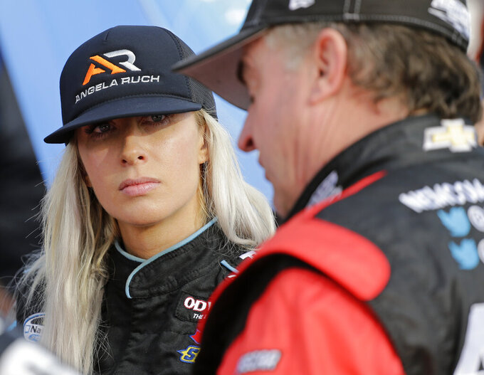 Angela Ruch talks with a crew member in her garage during NASCAR Truck Series auto racing practice at Daytona International Speedway, Thursday, Feb. 14, 2019, in Daytona Beach, Fla. (AP Photo/Terry Renna)