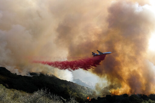 An air tanker drops retardant on a wildfire Wednesday, Oct. 13, 2021, in Goleta, Calif. A wildfire raging through Southern California coastal mountains threatened ranches and rural homes and kept a major highway shut down Wednesday as the fire-scarred state faced a new round of dry winds that raise risk of flames. The Alisal Fire covered more than 22 square miles (57 square kilometers) in the Santa Ynez Mountains west of Santa Barbara. (AP Photo/Ringo H.W. Chiu)
