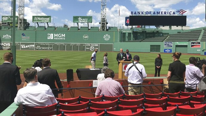 Massachusetts Gov. Charlie Baker, at podium, speaks about Phase 3 of the state's reopening plan during a media availability at Fenway Park, Thursday, July 2, 2020, in Boston. In most of the state, Phase 3 will begin on Monday. In Boston, the Phase 3 reopening will begin a full week later, on July 13. (AP Photo/Jimmy Golen)