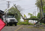 A utility crew works to clear a roadway of storm debris in Newburgh, N.Y., Wednesday, May 16, 2018. Powerful storms pounded the Northeast on Tuesday with torrential rain and marble-sized hail, leaving thousands of homes and businesses without power. (AP Photo/Seth Wenig)