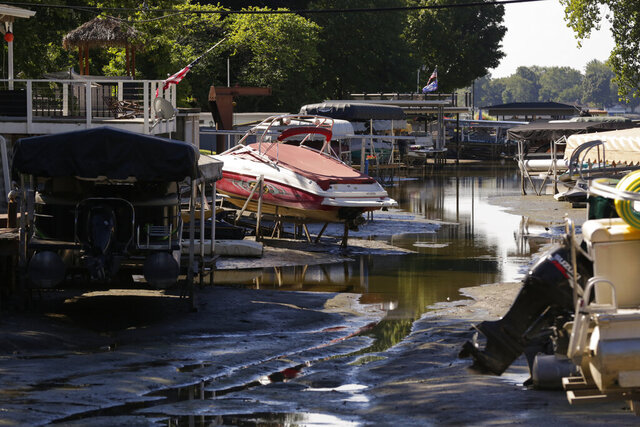 Boats sit well above the water level of the Tippecanoe River on a man-made canal, Friday, Sept. 4, 2020 in Monticello, Ind. (Nikos Frazier/Journal & Courier via AP)