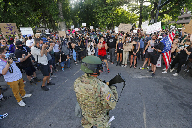 Protesters conduct a peaceful demonstration while a Utah National Guardsman watches Tuesday, June 2, 2020, in Salt Lake City. A peaceful protest over George Floyd's death made its way through downtown after the mayor announced a new weeklong curfew. (AP Photo/Rick Bowmer)