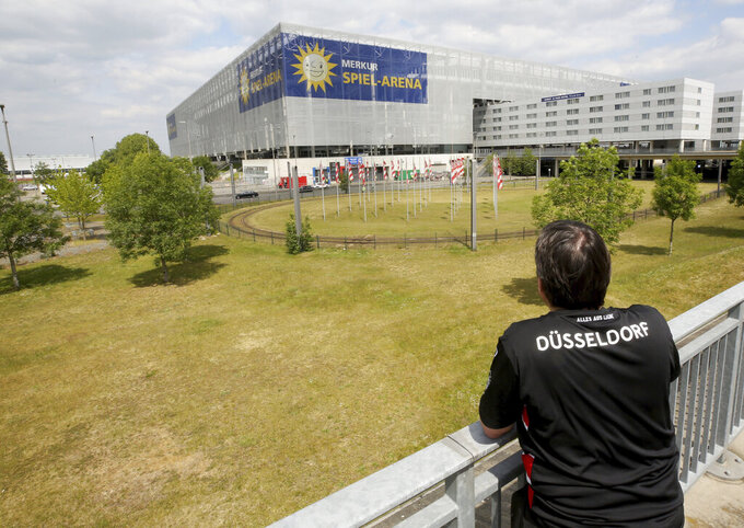 A lone fan of Fortuna Duesseldorf watches from far the Merkur Spiel-Arena prior to the Bundesliga soccer match between Duesseldorf and Paderborn in Duesseldorf, Germany, Saturday, May 16, 2020. The German Bundesliga becomes the world's first major soccer league to resume after a two-month suspension because of the coronavirus pandemic. (Roland Weihrauch/DPA via AP)