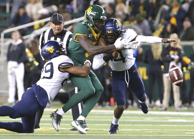 Baylor wide receiver Denzel Mims (5) is hit West Virginia safety Josh Norwood (4) and safety Sean Mahone (29) during the first half of an NCAA college football game in Waco, Texas, Thursday, Oct. 31, 2019. Norwood was ejected for targeting. (AP Photo/Jerry Larson)