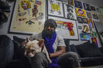 Painter Guy Stanley Philoche, a 43-year-old Haitian immigrant and star in the New York art world, sits with his dog Picasso at their East Harlem home next to a wall of art collected from other artist, Thursday Nov. 19, 2020, in New York. After a hugely successful gallery show, Philoche wanted to treat himself to a fancy $15,000 watch, instead he bought the works of fellow artists struggling in the pandemic.