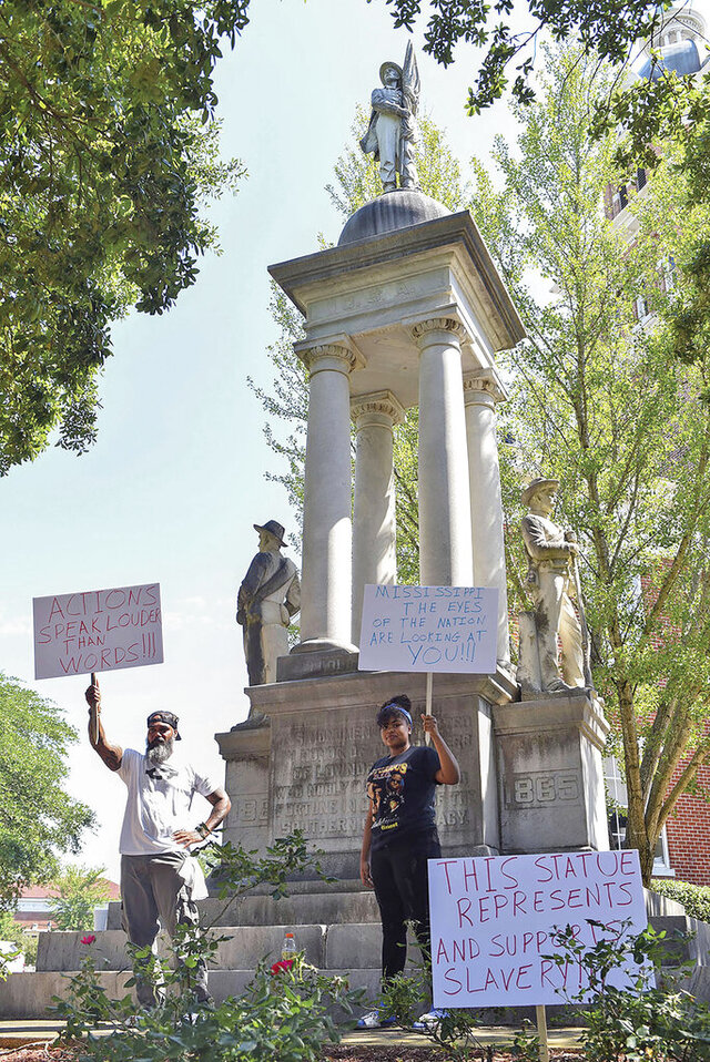 John Lewis, left, and Sonniah Ramirez, 12, protest for the removal of the Confederate monument that stands on the Lowndes County Courthouse lawn, Monday, June 15, 2020 in Columbus, Miss. Lewis was protesting by himself when Ramirez approached him and offered to join in his protest. (Claire Hassler/The Commercial Dispatch, via AP)