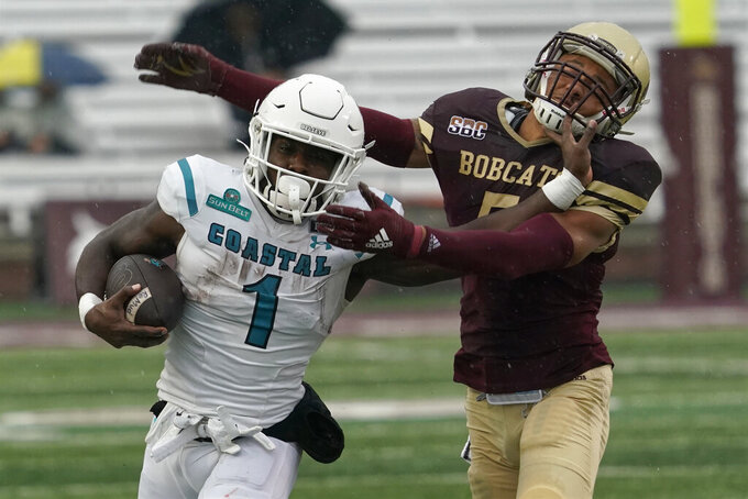 Coastal Carolina's CJ Marable (1) runs past Texas State's Kevin Anderson (5) during the first half of an NCAA college football game in Austin, Texas, Saturday, Nov. 28, 2020. (AP Photo/Chuck Burton)