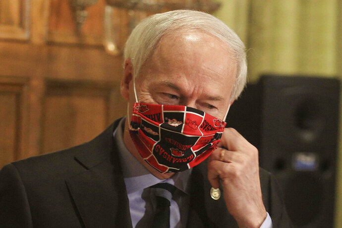 FILE - In this April 27, 2020 file photo, Gov. Asa Hutchinson takes off his Arkansas Razorbacks facemark as he arrives for the daily coronavirus briefing at the state Capitol in Little Rock. Hutchinson issued the order Thursday, July, 16, 2020, effective Monday, July 20, requiring people to wear masks in public throughout the state, which is dealing with a surge in coronavirus cases. The governor issued the order after weeks of resisting such a requirement. (Staton Breidenthal/Arkansas Democrat-Gazette via AP, File)