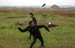 A protester hurls stones near the fence of the Gaza Strip border with Israel, marking first anniversary of Gaza border protests east of Gaza City, Saturday, March 30, 2019. Tens of thousands of Palestinians gathered Saturday at rallying points near the Israeli border to mark the first anniversary of weekly protests in the Gaza Strip, as Israeli troops fired tear gas and opened fire at small crowds of activists who approached the border fence.  (AP Photo/Adel Hana)