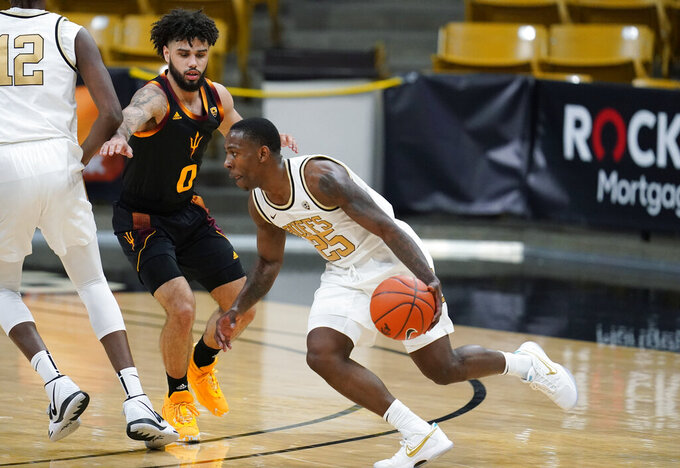 Colorado guard McKinley Wright IV, right, drives the lane as Arizona State guard Holland Woods defends in the first half of an NCAA college basketball game Thursday, March 4, 2021, in Boulder, Colo. (AP Photo/David Zalubowski)