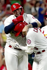St. Louis Cardinals' Yadier Molina, top, congratulates teammate Dylan Carlson on his grand slam during the eighth inning of a baseball game against the San Diego Padres Friday, Sept. 17, 2021, in St. Louis. (AP Photo/Jeff Roberson)