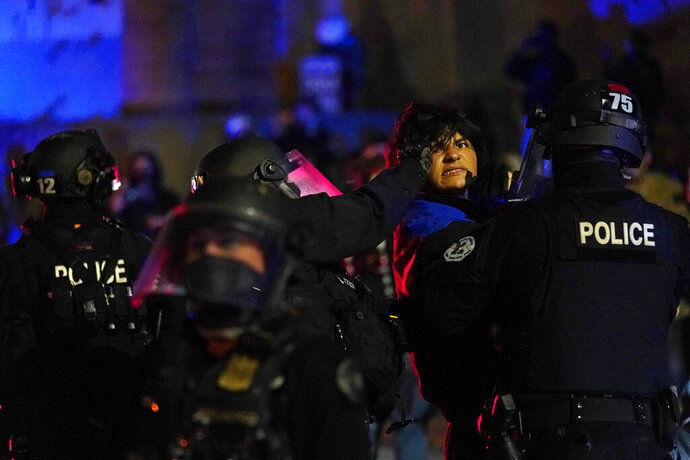 Portland police detain a man during protests, Saturday, Sept. 26, 2020, in Portland. The protests, which began over the killing of George Floyd, often result frequent clashes between protesters and law enforcement. (AP Photo/John Locher)