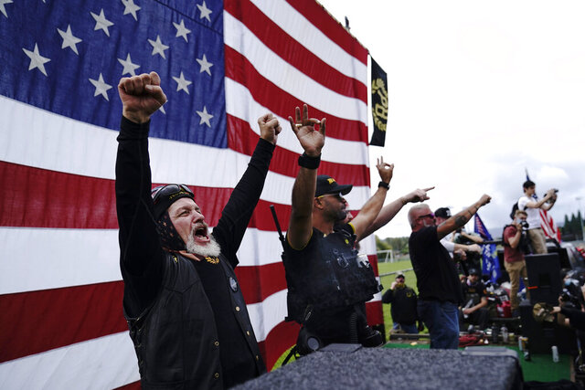"FILE - In this Sept. 26, 2020 file photo, members of the Proud Boys, including leader Enrique Tarrio, second from left, gesture and cheer on stage as they and other right-wing demonstrators rally in Portland, Ore. President Donald Trump didn't condemn white supremacist groups and their role in violence in some American cities this summer. Instead, he said the violence is a ""left-wing"