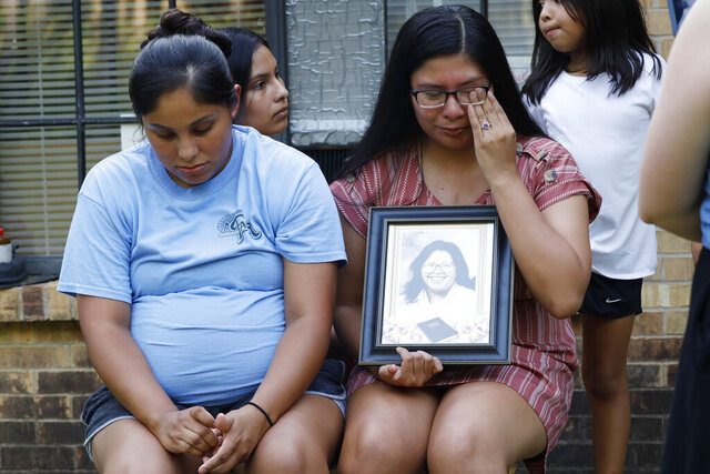 Kristina Taylor, 18, cries as she holds a portrait of her late mother, Sharon Taylor, while she and her older sister Kristi Wishork, 25, recall the care their mother had for her children and grandchildren, Tuesday, July 21, 2020 at their home in Tucker, Miss. Taylor, 53, died of coronavirus at the University of Mississippi Medical Center in Jackson on June 26 after two weeks in the hospital. She never saw her daughter Kristina, the class valedictorian at Choctaw Central High School, graduate. (AP Photo/Rogelio V. Solis)