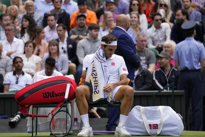 Switzerland's Roger Federer wipes his face with a towel during the men's singles quarterfinals match against Poland's Hubert Hurkacz on day nine of the Wimbledon Tennis Championships in London, Wednesday, July 7, 2021. (AP Photo/Kirsty Wigglesworth)