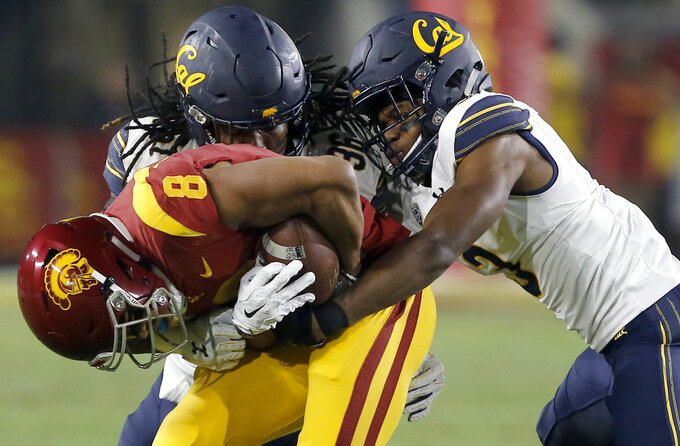 Southern California wide receiver Amon-Ra St. Brown, left, is stopped by California linebacker Alex Funches, center, and cornerback Elijah Hicks, right, after a reception during the first half of an NCAA college football game in Los Angeles, Saturday, Nov. 10, 2018. (AP Photo/Alex Gallardo)