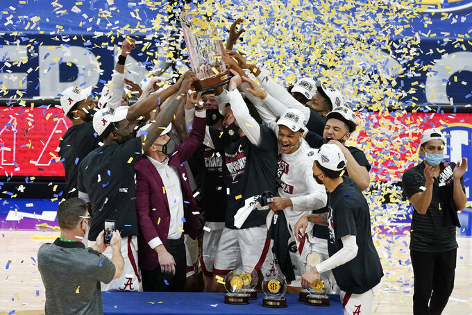 Alabama head coach Nate Oats and players lift the trophy after the championship game of the NCAA college basketball Southeastern Conference Tournament between Alabama and LSU Sunday, March 14, 2021, in Nashville, Tenn. Alabama won 80-79. (AP Photo/Mark Humphrey)