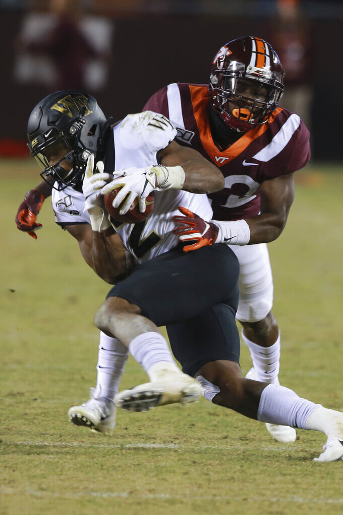 Virginia Tech defensive back Chamarri Conner, right, tries to wrap Wake Forest wide receiver Kendall Hinton (2) during the second half of an NCAA college football game in Blacksburg, Va., Saturday, Nov. 9, 2019. Virginia Tech defeated Wake Forest 36-17. (AP Photo/Steve Helber)