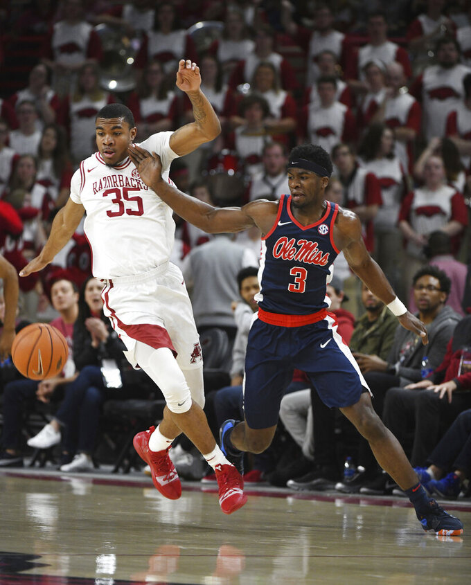 Arkansas forward Reggie Chaney (35) and Mississippi guard Terence Davis go after the ball during the first half of an NCAA college basketball game, Saturday, March 2, 2019 in Fayetteville, Ark. (AP Photo/Michael Woods)