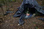 A migrant rests in a tent improvised from plastic sheets at a makeshift camp in a forest outside Velika Kladusa, Bosnia, Friday, Sept. 25, 2020.(AP Photo/Kemal Softic)