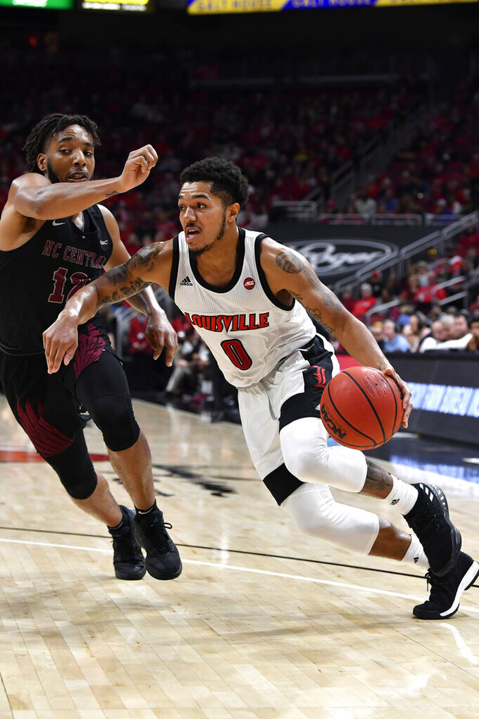 Louisville guard Lamarr Kimble (0) drives past the defense of North Carolina Central guard Jordan Perkins (12) during the second half of an NCAA college basketball game in Louisville, Ky., Sunday, Nov. 17, 2019. Louisville won 87-58. (AP Photo/Timothy D. Easley)