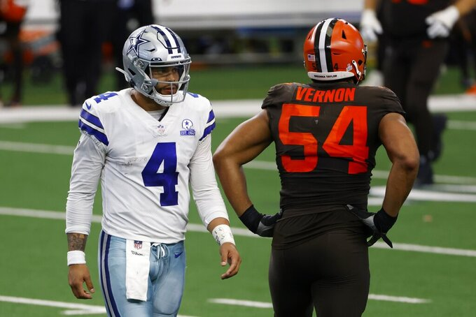 Dallas Cowboys quarterback Dak Prescott (4) walks past Cleveland Browns defensive end Olivier Vernon (54) on his way to the sideline after throwing an interception late in the second half of an NFL football game in Arlington, Texas, Sunday, Oct. 4, 2020. (AP Photo/Ron Jenkins)