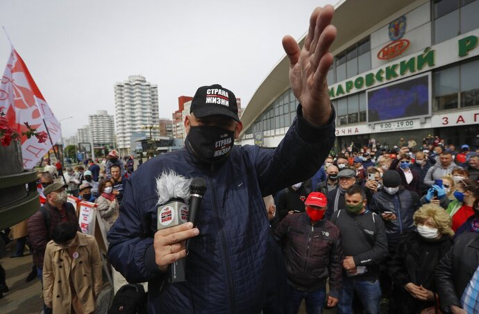 An opposition activist Sergei Tikhovoski, wearing a face mask to protect against coronavirus, gestures as he speaks to people gathered to sign up and support potential presidential candidates in the upcoming presidential elections in Minsk, Belarus, Sunday, May 24, 2020. The presidential campaign is underway in Belarus despite the coronavirus outbreak after the parliament and government refused to postpone the election scheduled for August 9. (AP Photo/Sergei Grits)
