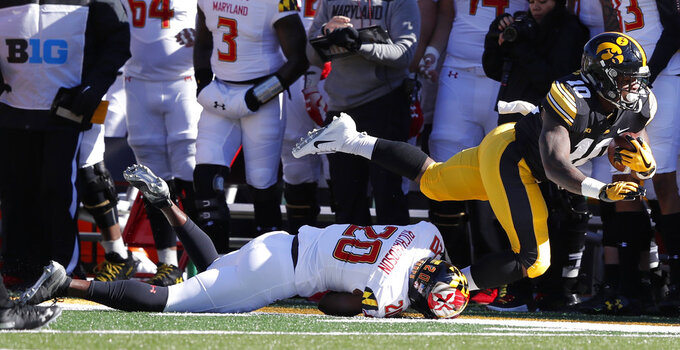 Iowa running back Mekhi Sargent (10) is tackled by Maryland defensive back Antwaine Richardson during the first half of an NCAA college football game, Saturday, Oct. 20, 2018, in Iowa City, Iowa. (AP Photo/Charlie Neibergall)