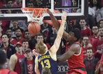 Rutgers center Shaquille Doorson dunks over Michigan forward Ignas Brazdeikis (13) during the first half of an NCAA college basketball game Tuesday, Feb. 5, 2019, in Piscataway, N.J. (AP Photo/Bill Kostroun)