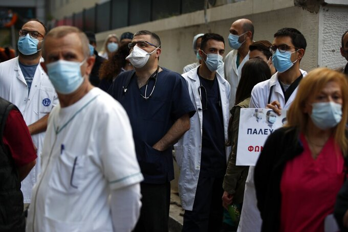 Health workers wearing face masks to protect against the spread of the coronavirus, take part in a protest at Evangelismos hospital in Athens, Thursday, Nov. 12, 2020.  State health workers' union staged protests at several hospitals around the country to demand more hiring. Greece has imposed a nationwide nightly curfew as the number of COVID-19 cases in the country continues to surge despite a lockdown. (AP Photo/Thanassis Stavrakis)