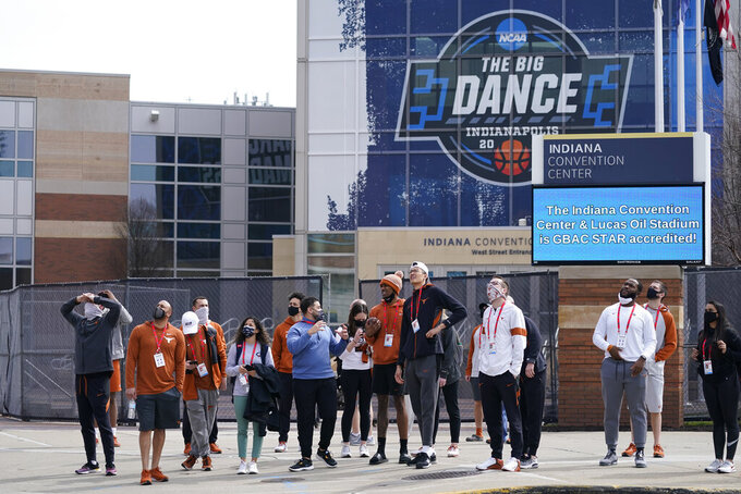 The Texas basketball team looks at the NCAA bracket for the NCAA college basketball tournament on the side of the JW Marriott building, Wednesday, March 17, 2021, in Indianapolis. (AP Photo/Darron Cummings)