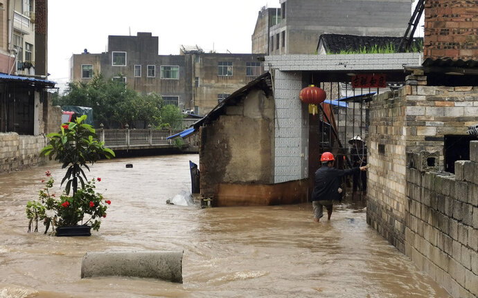 In this June 24, 2020, photo, a man walks through a flooded village in Huishui County in southwestern China's Guizhou Province.  More than 20 people have died this year in seasonal rains in southern China that swell rivers and flood towns and agricultural fields (Chinatopix via AP)