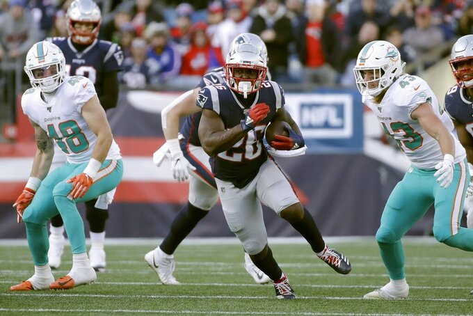 New England Patriots running back Sony Michel, center, runs from Miami Dolphins linebackers Calvin Munson, left, and Andrew Van Ginkel, right, in the first half of an NFL football game, Sunday, Dec. 29, 2019, in Foxborough, Mass. (AP Photo/Elise Amendola)