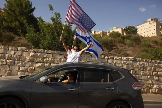 Supporters of U.S. President Donald Trump for re-election wave an American and an Israeli flag from a car headed for a rally outside of the U.S. Embassy, in Jerusalem, Tuesday, Oct. 27, 2020. (AP Photo/Maya Alleruzzo)
