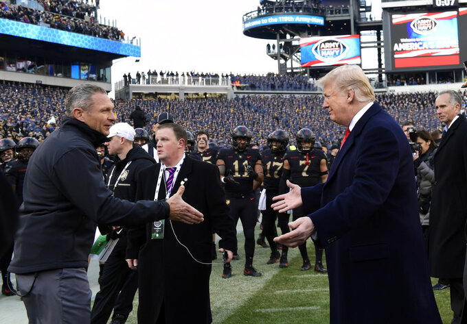 President Donald Trump, right, greets Army coach Jeff Monken before the Army-Navy NCAA college football game in Philadelphia, Saturday, Dec. 8, 2018. (AP Photo/Susan Walsh)