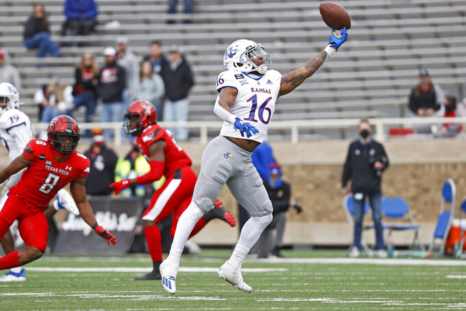 Kansas' Takulve Williams (16) drops a pass during the second half of an NCAA college football game against Texas Tech, Saturday, Dec. 5, 2020, in Lubbock, Texas. (AP Photo/Brad Tollefson)