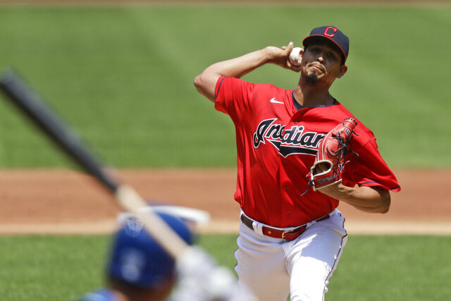 Cleveland Indians starting pitcher Carlos Carrasco, top, delivers to Kansas City Royals' Whit Merrifield in the first inning in a baseball game Sunday, July 26, 2020, in Cleveland. (AP Photo/Tony Dejak)