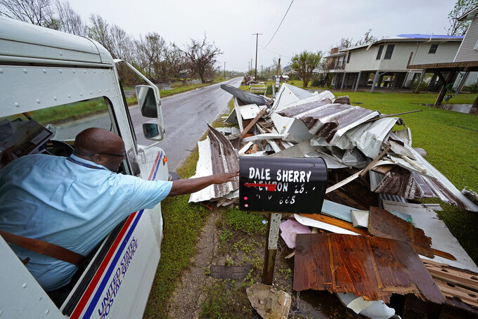 Derrick Campbell, postmaster for Montegut, La., delivers mail amidst destruction from Hurricane Ida, in Pointe-aux-Chenes, La., Tuesday, Sept. 14, 2021. (AP Photo/Gerald Herbert)