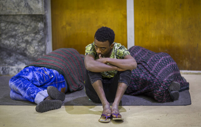 FILE - In this Friday, Dec. 22, 2017 file photo, Ethiopian Zeynu Abebe, 19, sits in between two others upon his arrival after being deported from Saudi Arabia, at the airport in Addis Ababa, Ethiopia. A new report released Friday, Sept. 2, 2020 by Amnesty International describes widespread abuses and squalid detention conditions facing thousands of migrants from Ethiopia in Saudi Arabia. (AP Photo/Mulugeta Ayene, File)