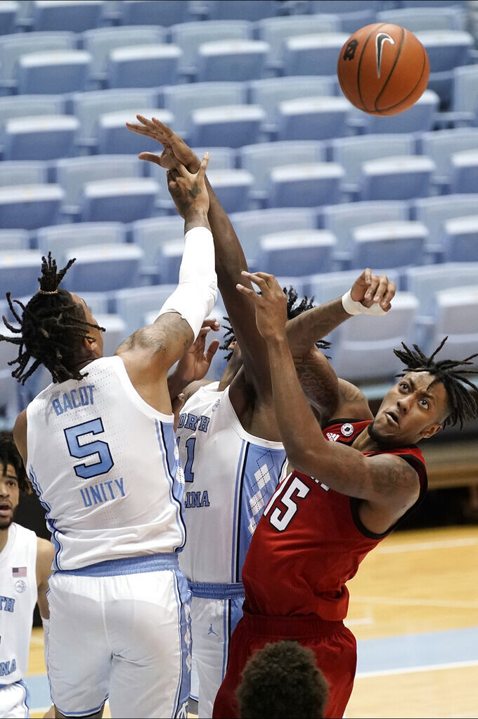 North Carolina forward Armando Bacot (5) and forward Day'Ron Sharpe struggle with North Carolina State forward Manny Bates (15) during the second half of an NCAA college basketball game in Chapel Hill, N.C., Saturday, Jan. 23, 2021. (AP Photo/Gerry Broome)