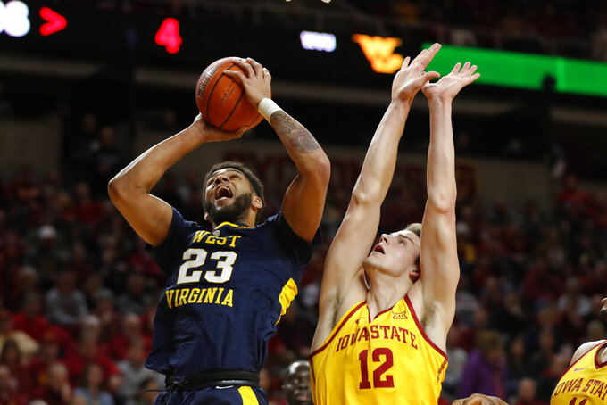 West Virginia forward Esa Ahmad, left, shoots over Iowa State forward Michael Jacobson during the first half of an NCAA college basketball game Wednesday, Jan. 30, 2019, in Ames, Iowa. (AP Photo/Charlie Neibergall)